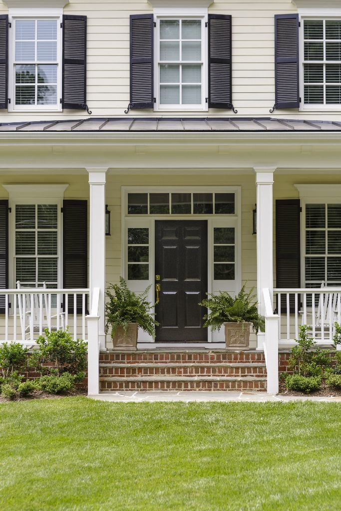 White colonial house with a porch and plants